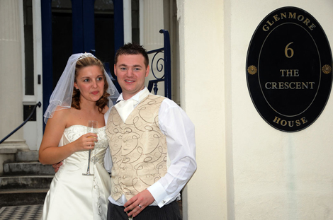 Happy newly-weds standing beside the gates and sign for Glenmore House a fine Surrey wedding venue in Surbiton conservation area