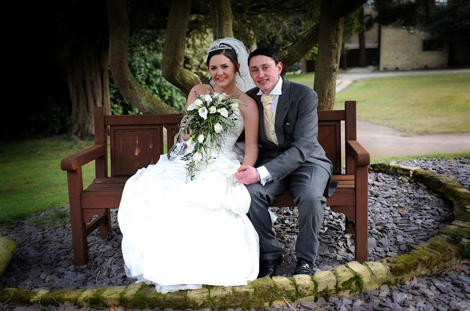 A lovely wedding photo of happy newly-weds sitting on a bench in the grounds of the Selsdon Park Hotel Croydon by Surrey Lane wedding photography