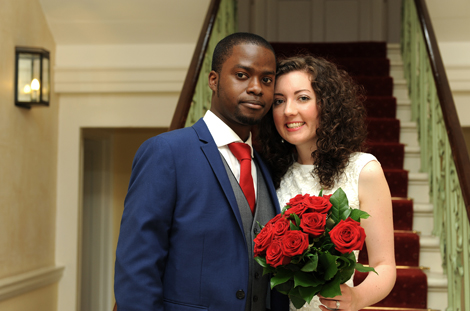 Happy and relaxed smart young newly-weds standing in the impressive hallway of Merton Register Office in Morden Park House a fine Georgian Surrey wedding venue