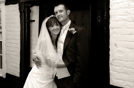 Lovely romantic wedding photograph of the happy relaxed couple having a hug at The Talbot, Ripley, the historic coaching inn Surrey wedding venue