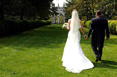 Beautiful romantic picture of the wedding couple walking along the lawn to the wonderful Gothic Temple folly at Painshill Park Cobham Surrey wedding