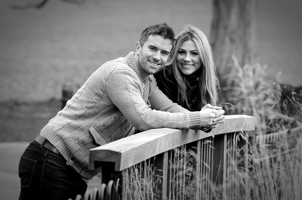 Beautiful smiling couple in Brockwell Park relaxing on a bridge in this pre wedding picture captured by Surrey wedding photographers on a lovely spring day