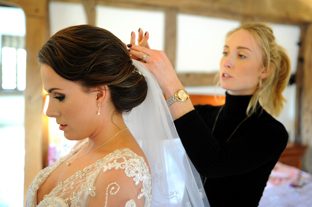 Beautiful Bride waits in the bridal suite at the beautiful Surrey wedding venue Cain Manor as her beautician attaches her wedding veil