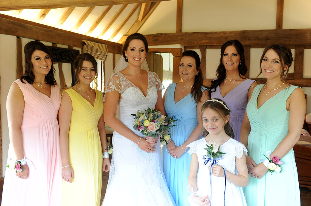 Surrey Bride poses with her bright colourfully dressed Bridesmaids before leaving the Cain Manor bridal suite for the Music Room marriage ceremony