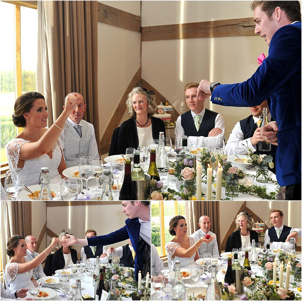 A Bride at the head table in the Music Room at Surrey wedding venue Cain Manor being entertained by a slight of hand magician
