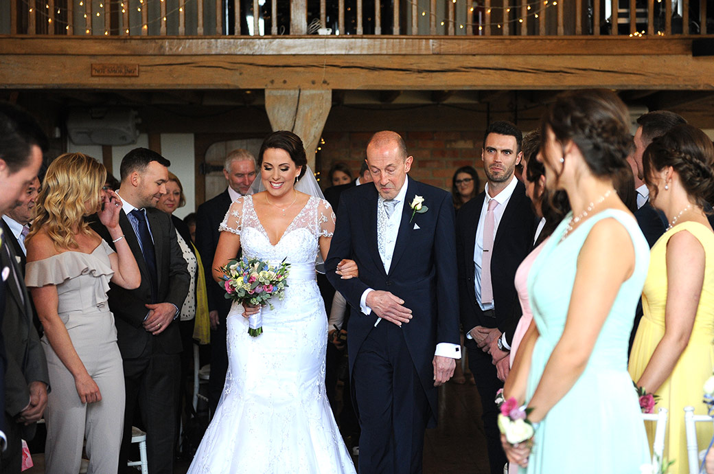 An excited Bride captured at the lovely Surrey wedding venue Cain Manor on her father's arm as she walks down the aisle of the Music Room