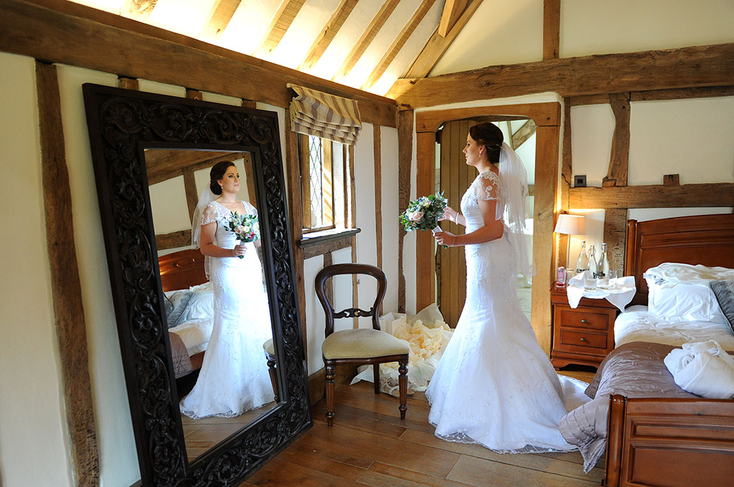 A beautiful bride at the delightful Surrey wedding venue Cain Manor makes a final check in the bridal suite mirror before leaving for the Music Room