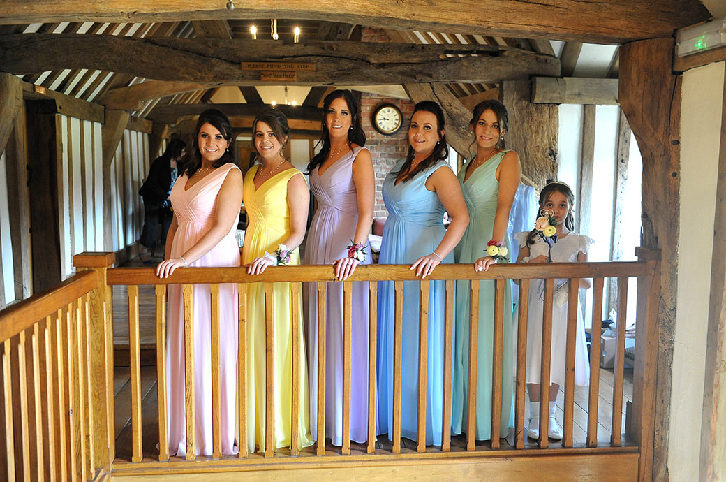 Bridesmaids strike a pose at the top of the oak stairs at Surrey wedding venue Cain Manor in their beautifully colourful dresses