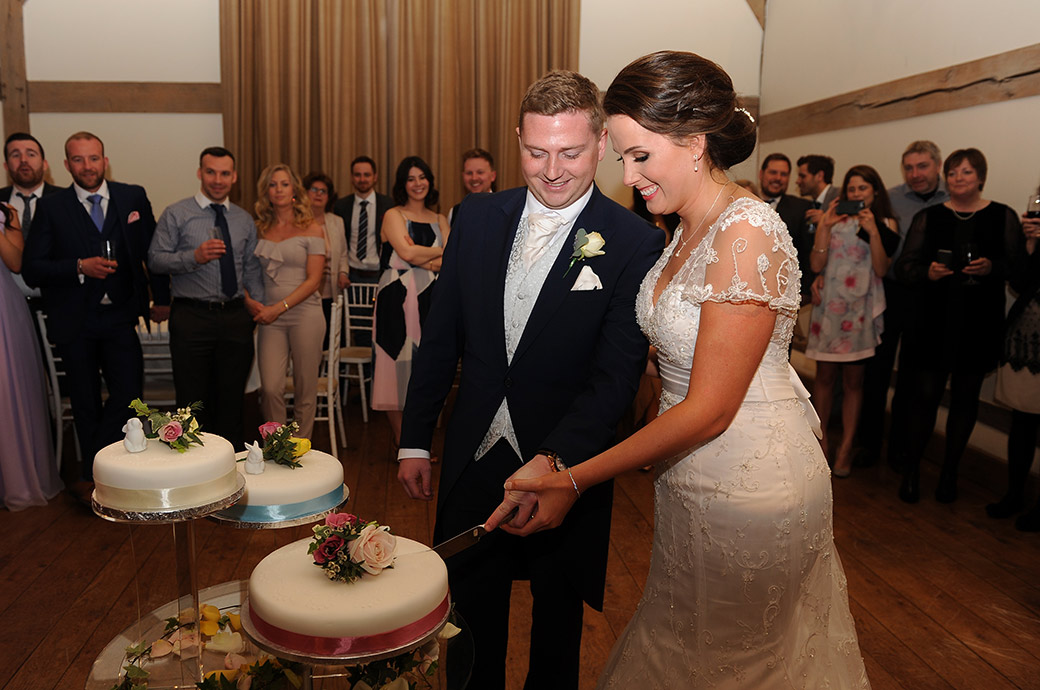 Excited Bride and Groom at the fabulous Cain Manor in Surrey cut their wedding cake on the dance floor in the Music Room
