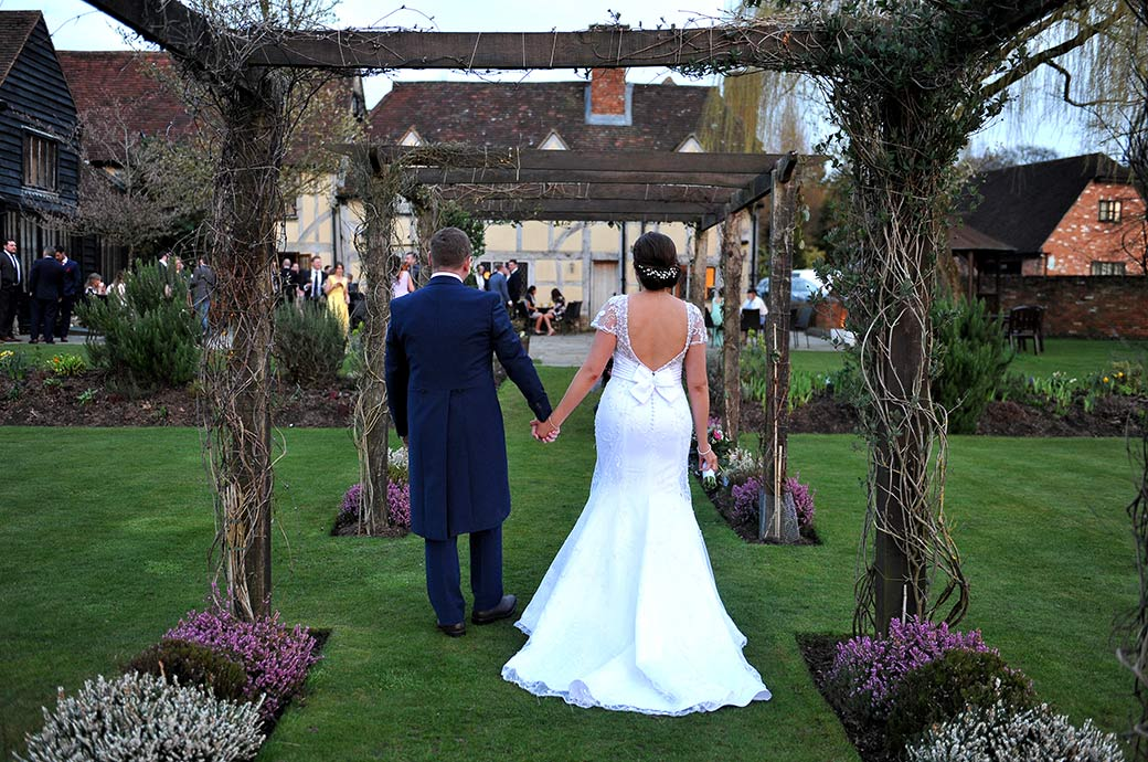 Couple walk hand in hand under the rose arbour back towards their guests after their romantic walk around the picturesque grounds of Cain Manor in Surrey