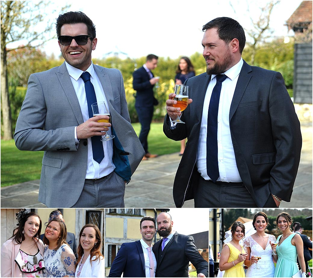 Wedding guests out on the patio terrace enjoying drinks after the marriage ceremony  at Surrey wedding venue Cain Manor in Headley Down