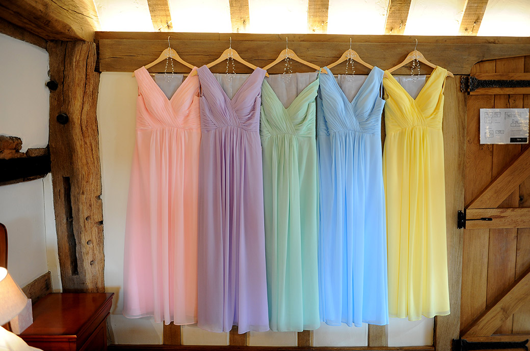 Beautiful pink mauve green blue and yellow bridesmaid dresses hanging up in the bridal suite at Cain Manor wedding in Headley Down Surrey