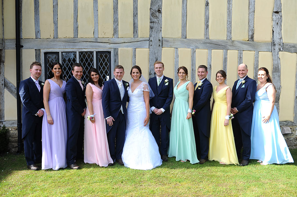 Newlyweds at Cain Manor in Headley Down Surrey in this group wedding photo with their smart groomsmen and Bridesmaids in their colourful dresses