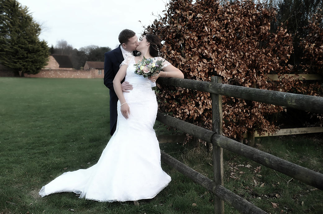Relaxed newlyweds captured in the grounds of Surrey wedding venue Cain Manor as they stand by a wooden fence and romantically kiss