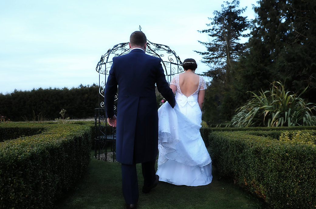 Rear view of a Groom at Surrey wedding venue Cain Manor holding the Bride's dress as they walk across the lawn to the wrought iron pergola
