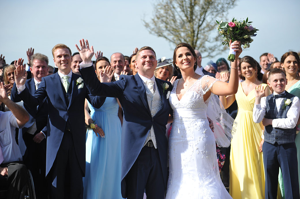 Smiling couple and guests waving at the Surrey Lane wedding photographer leaning out of a bedroom window at the Cain Manor Surrey wedding venue