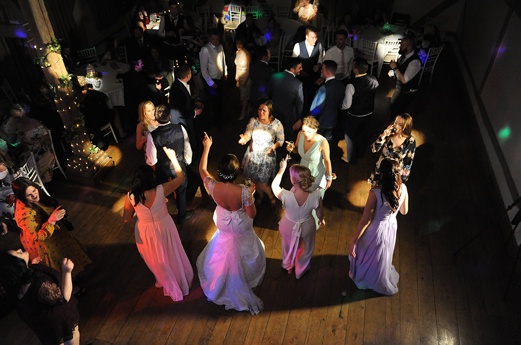 Atmospheric photo taken from the Music Room minstrel gallery at Surrey wedding venue Cain Manor of a bride and guests dancing in the disco lights