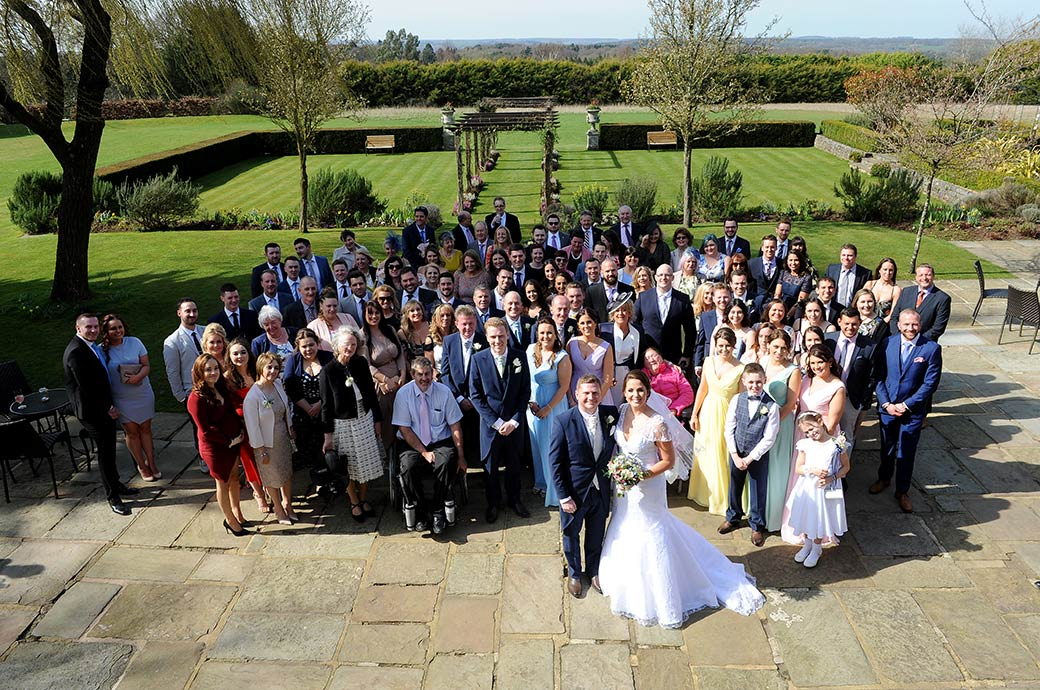 Bride and Groom star in the everyone at the wedding group photograph taken on the patio at Cain Manor Surrey from a bedroom window