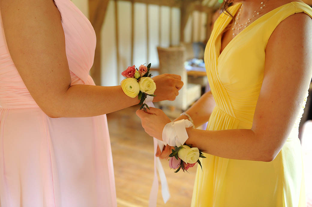 Bridesmaid fastens up a lovely flower corsage for another bridesmaid at Surrey wedding venue Cain Manor in Headley Down