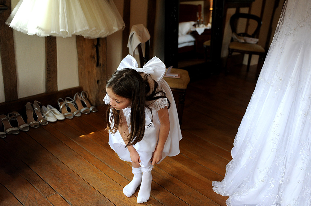 Pretty nymph like flower girl at the Cain Manor Surrey wedding venue dressed in white with a big white bow adjusting her socks in the bridal suite