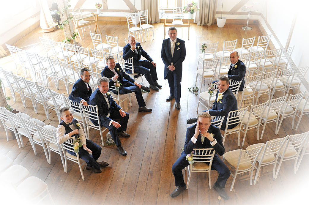 Groom poses with his Groomsmen in the Music Room prior to the marriage ceremony captured at Surrey wedding venue Cain Manor from the minstrel gallery