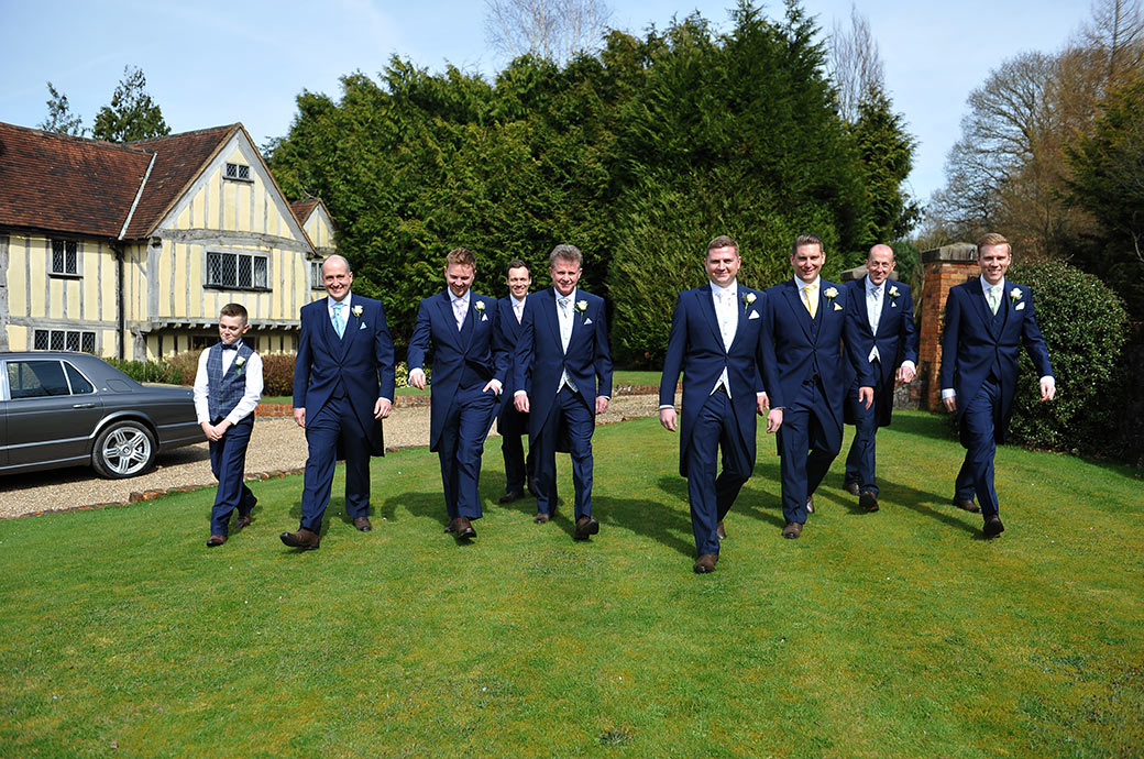 The Groom accompanied by his Groomsmen strides across the lawn for a walk around the picturesque grounds of picturesque wedding venue Cain Manor in Surrey