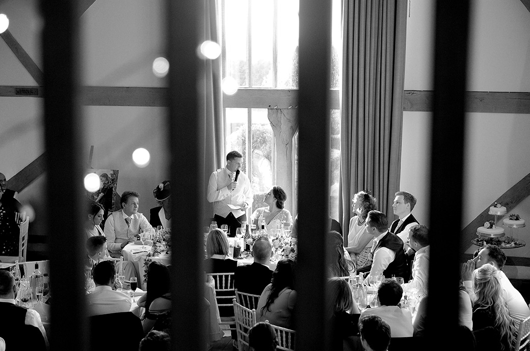 Evocative picture of a groom addressing his wife during the wedding speeches captured at Cain Manor Surrey through the banister of the minstrel gallery