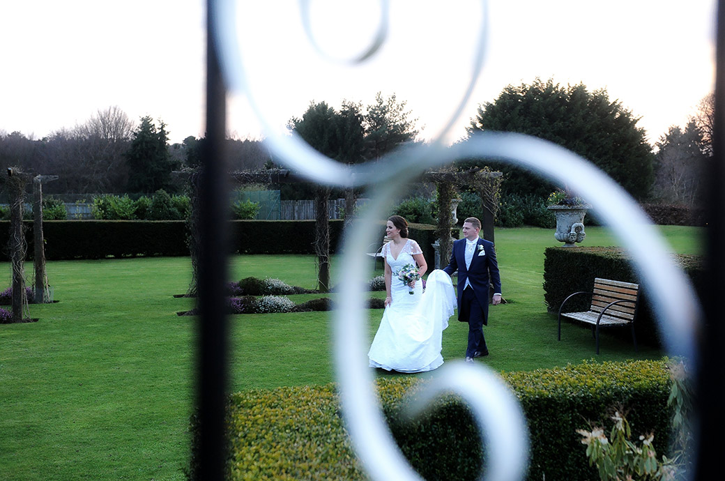Groom holds the Bride's dress as they walk across the lawn at the delightful and charming Surrey wedding venue Cain Manor in Headley Down