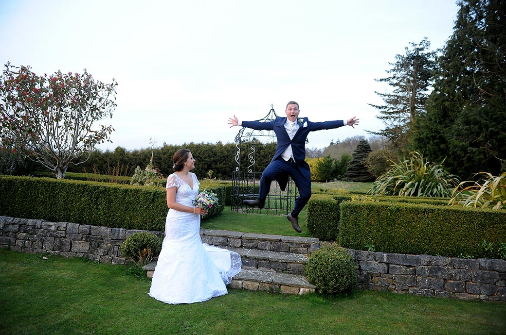 Funny wedding picture of a Groom taking a leap down the steps onto the lawn as his wife watches at the ever popular Surrey wedding venue Cain Manor
