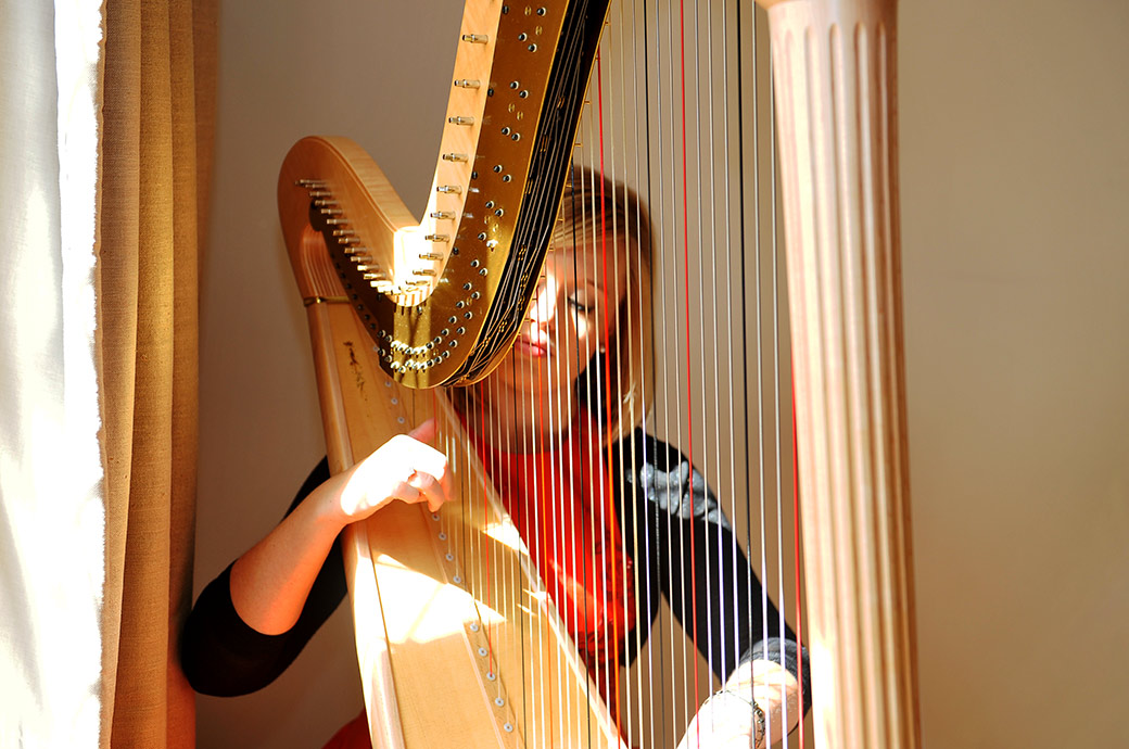 Evocative and atmospheric wedding photo taken in the Music Room at Surrey wedding venue Cain Manor of a harpist playing before a marriage ceremony