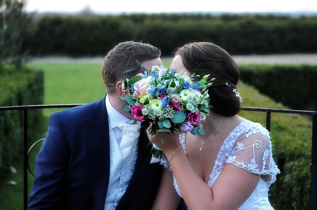 Fun newlyweds at the Cain Manor Surrey wedding venue have a sneaky kiss behind the Bride's bouquet as they sit on the ironwork garden seat