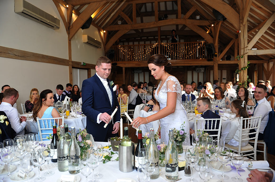 Newlywed couple at the start of the wedding breakfast at Surrey wedding venue Cain Manor light candles to symbolize the joining of families
