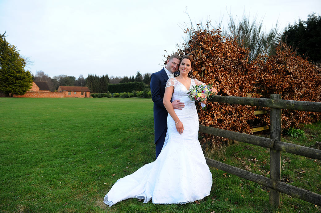 Content and relaxed newlywed couple captured in the grounds of Cain Manor Surrey as they stand by a wooden fence and copper coloured bush