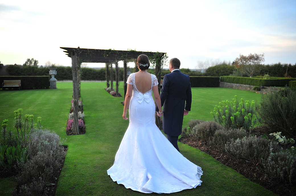 Romantic Bride and groom at the delightfully charming Surrey wedding venue Cain Manor hold hands as the walk on the lawn towards the rose arbour