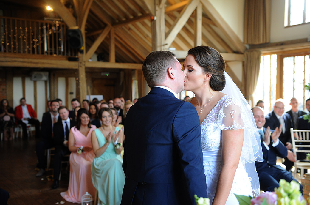 Bride and Groom hold hands as they kiss passionately after getting married in the atmospheric Music Room of picturesque Surrey wedding venue Cain Manor