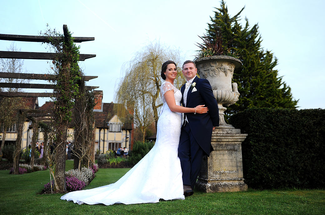 A very relaxed and happing looking Bride and groom stand by a large stone flowerpot beside a rose arbour in the tranquil Cain Manor grounds in Headley Down Surrey