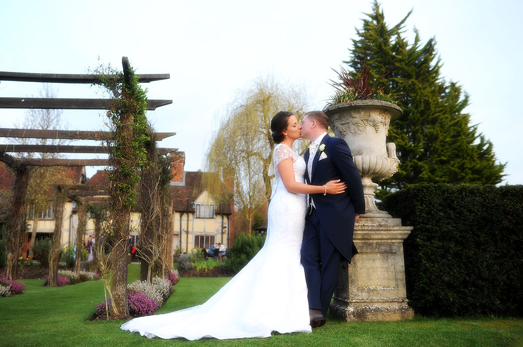 Bride and groom at Cain Manor in Surrey romantically kiss by a large stone flowerpot beside a rose arbour in the tranquil and picturesque garden
