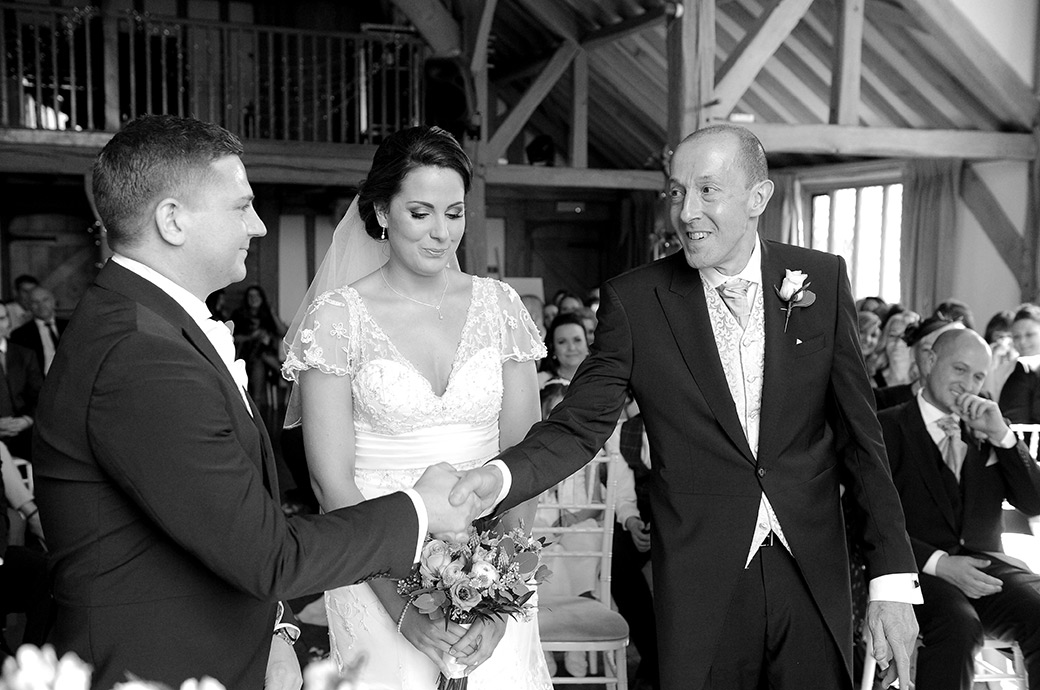 All smiles at the Cain Manor Surrey wedding venue as the Father of the Bride shakes the hand of the Groom in the aisle of the Music Room