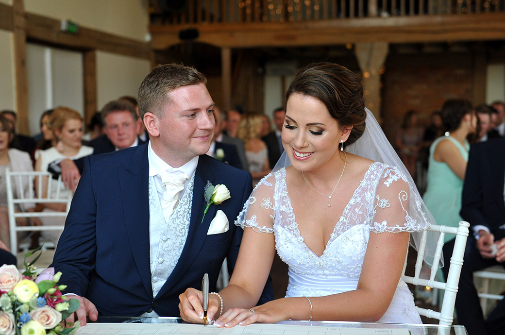 A happy Groom at the Cain Manor wedding venue in Surrey watches as his beautiful smiling bride signs the marriage register