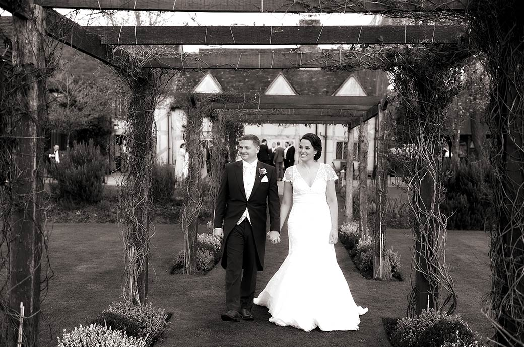 Smiling newlyweds captured as they walk hand in hand under the rustic rose arbour at the picturesque Surrey wedding venue Cain Manor