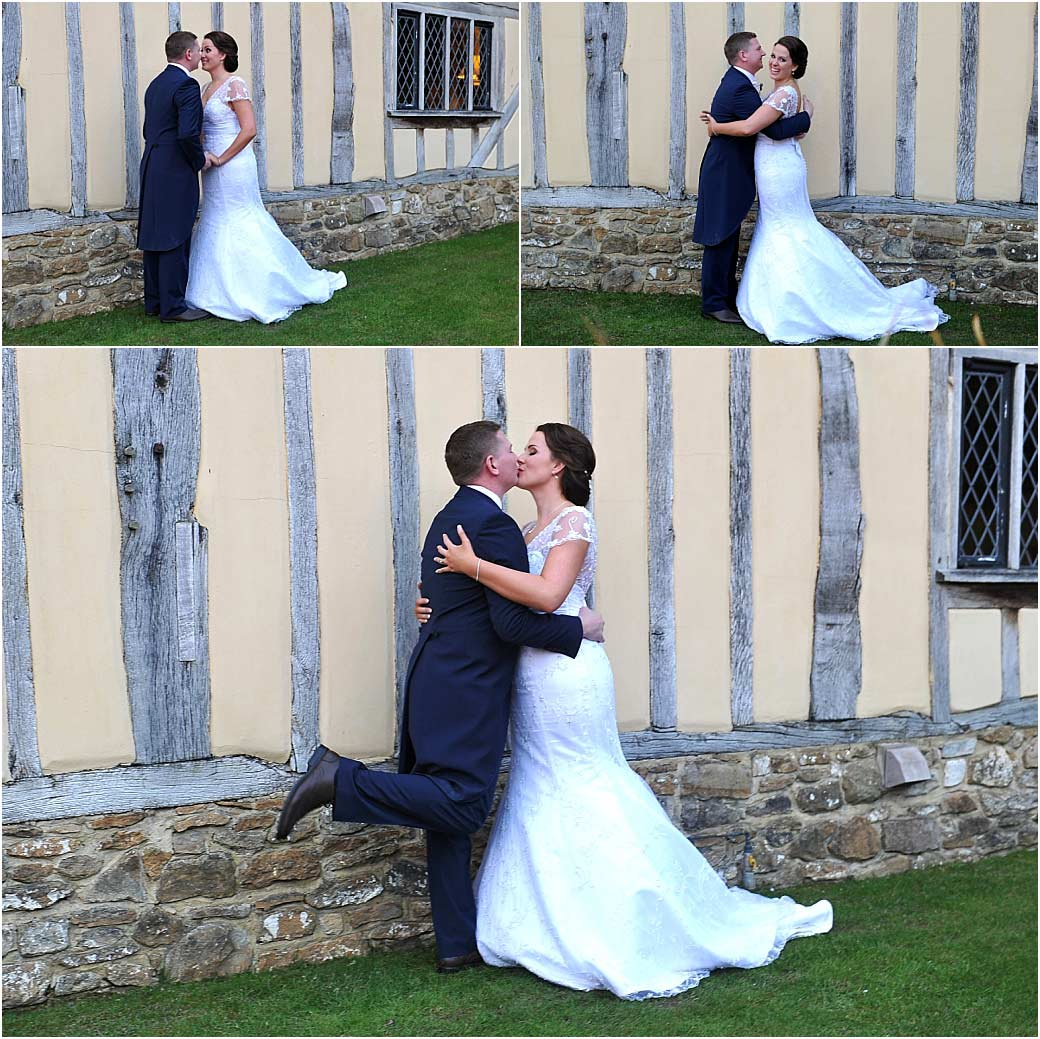 Newlyweds holding each other kissing and having fun in front of the distinctive weather beaten old beamed walls of the charming Surrey wedding venue Cain Manor