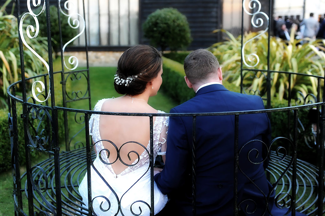 Wedding couple at Cain Manor in Surrey take a moment to sit down in the iron pergola and watch the world go by
