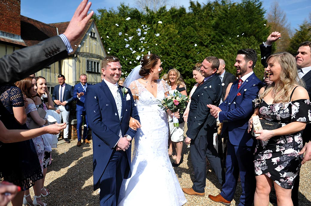 Fun and laughter at the charming and picturesque wedding venue Cain Manor in Headley Down Surrey during the confetti throwing on the patio