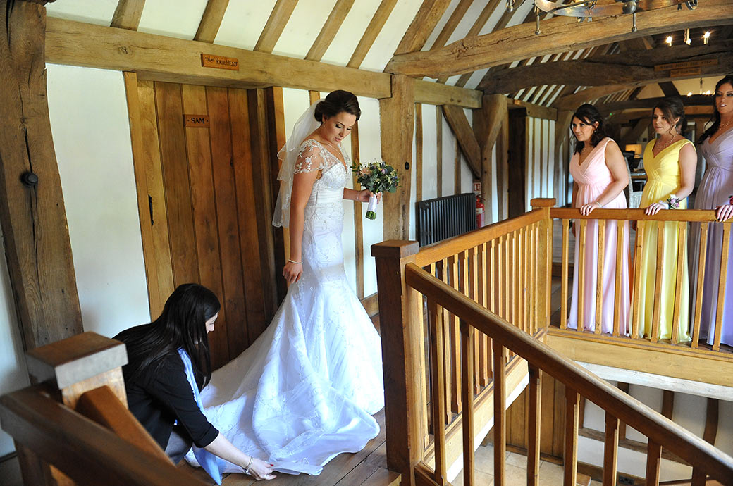 Final adjustments of the Bride's wedding dress on the oak staircase before she leaves for her marriage ceremony in the Music Room at Cain Manor Surrey