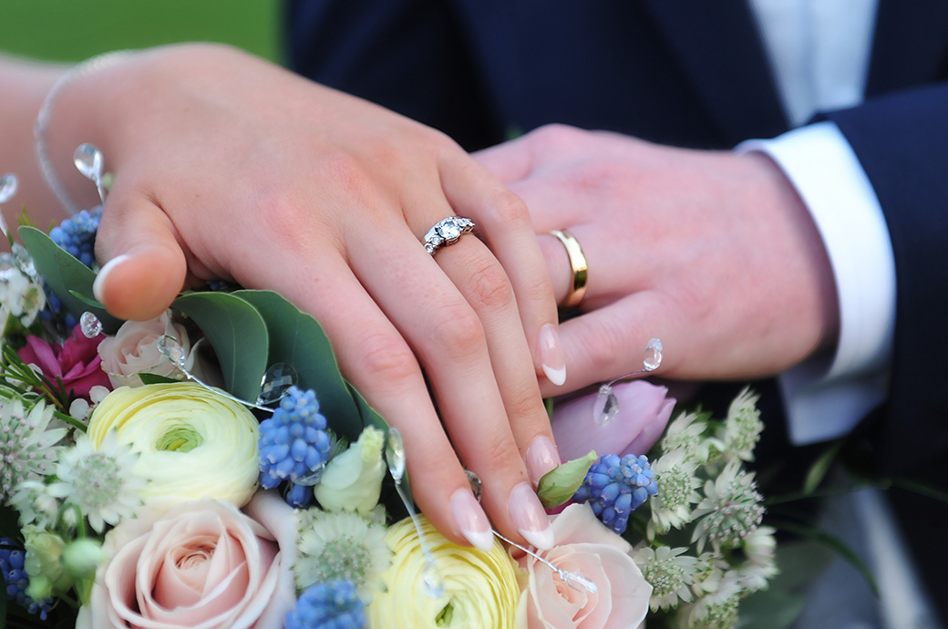 Bride and Groom in the grounds of Surrey venue Cain Manor show off their wedding rings with a pastel coloured rose bouquet background