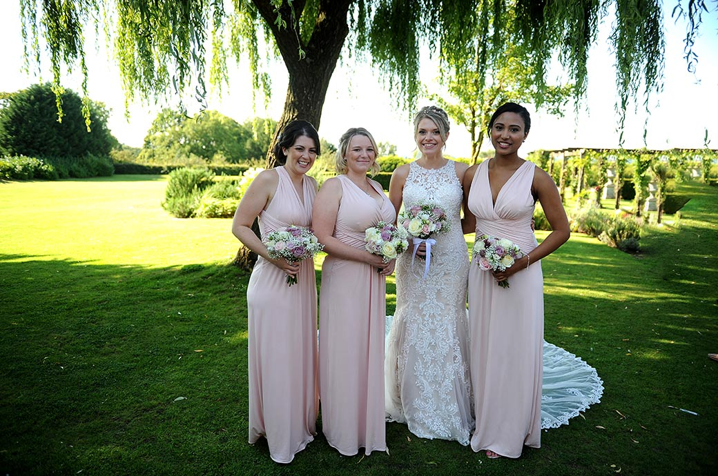 Bride and Bridesmaids pose for a traditional group wedding photo out on the lawn at the homely bijou Surrey wedding venue Cain Manor