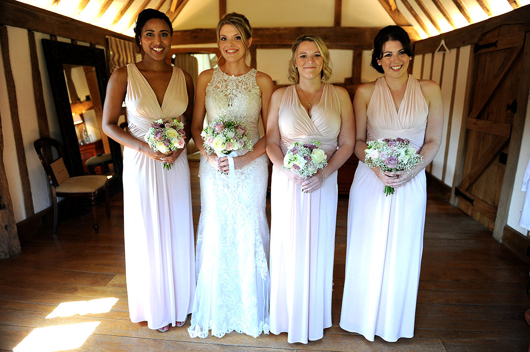 Happy smiling Bride and Bridesmaids at Surrey venue Cain Manor all dressed holding their wedding bouquets and ready to go the Music Room for the marriage ceremony