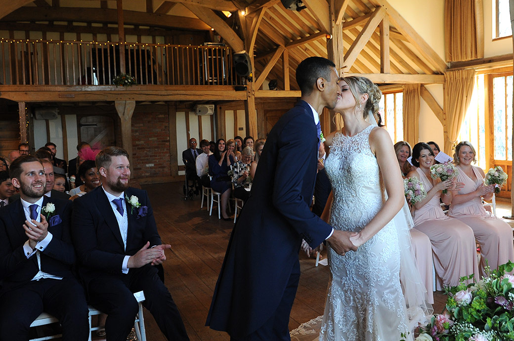 Bride and Groom romantically kiss at Cain Manor in Headley Down Surrey as they are announced husband and wife much to the delight of the wedding guests