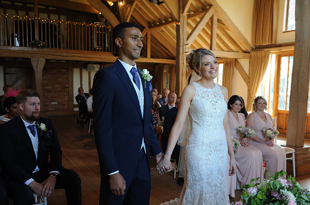 A beaming Bride and Groom standing in the Music Room at Surrey wedding venue Cain Manor look excitedly at the marriage registrar as they become husband and wife