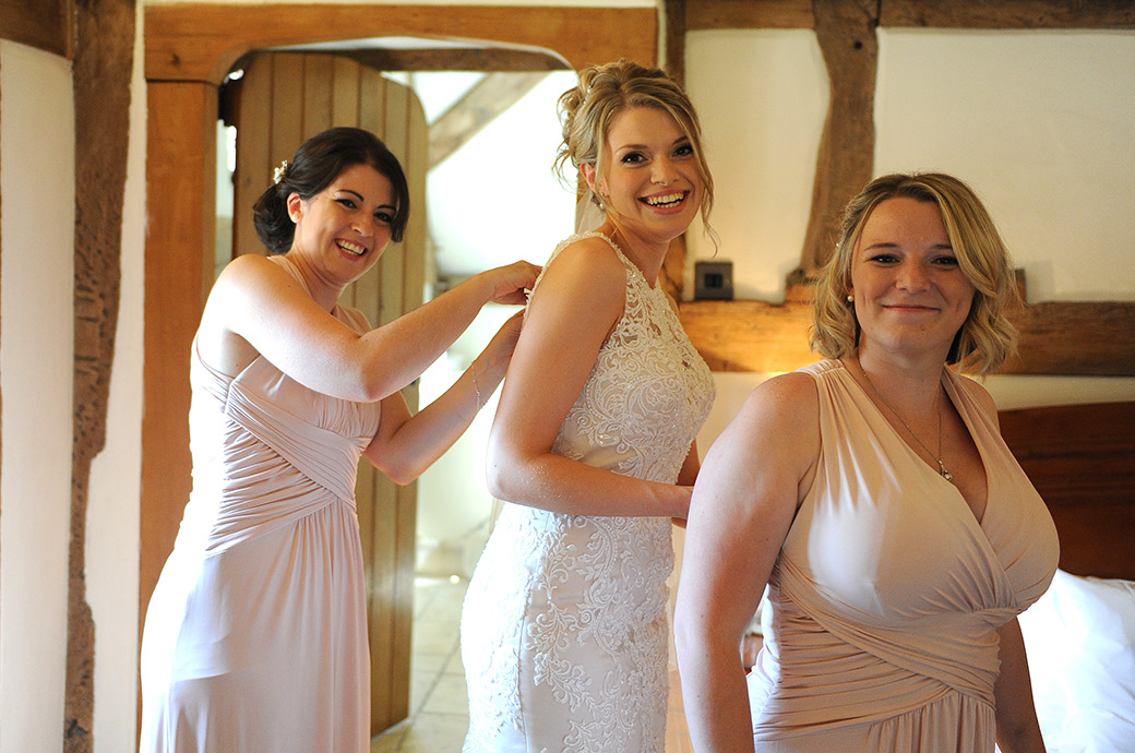 All hands on deck as a bridesmaid and Bride help to fasten up dresses in the bright and cosy Bridal Suite at Cain Manor a Surrey wedding venue in Headley Down